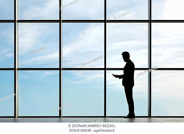 Silhouette of a man in a dark business suit in the window with the sky in the background