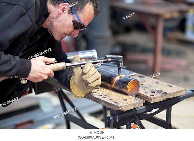 Worker using blow torch in shipyard workshop