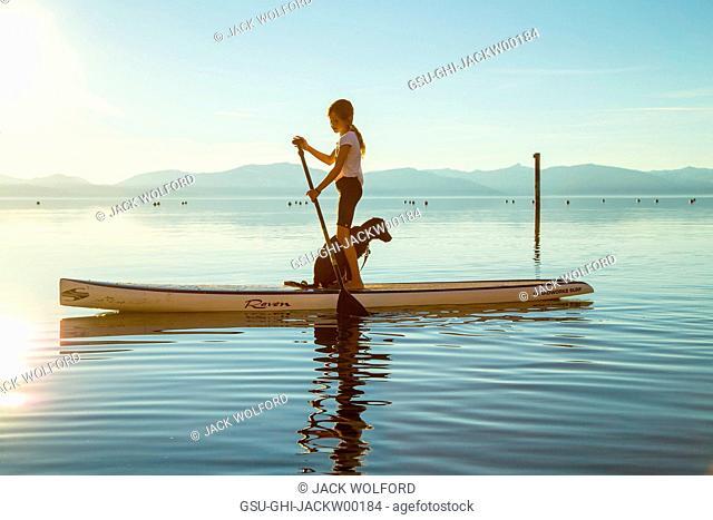 Young Girl and Dog on Paddle Board, Lake Tahoe, Nevada, USA