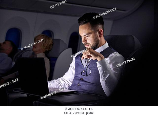 Serious businessman working at laptop on overnight airplane