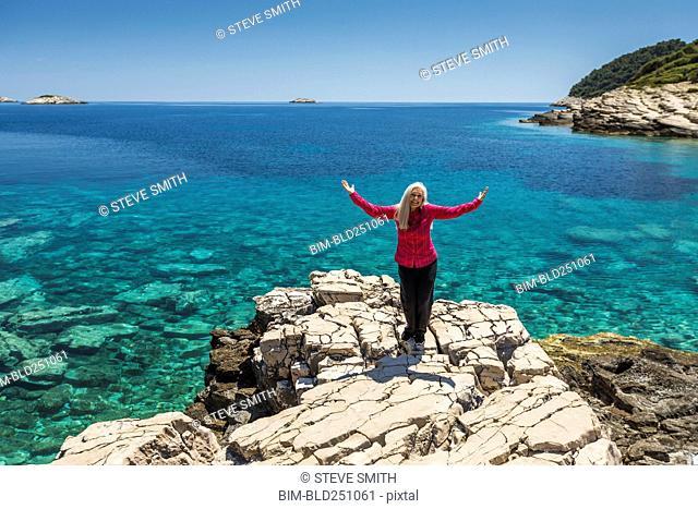 Caucasian woman posing on rock at lake