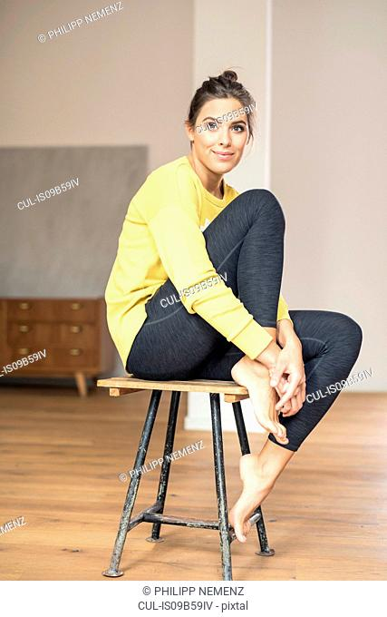 Portrait of young woman with knee up sitting on stool