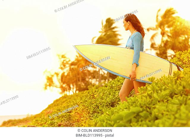 Pacific Islander woman carrying surfboard outdoors