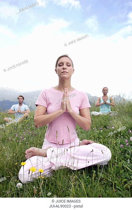 Group of people practicing yoga, Kleinwalsertal, Allgau, Germany