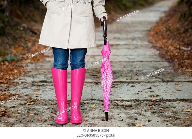 Woman with umbrella wearing rubber boots, Debica, Poland