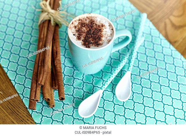 Still life of hot chocolate, cinnamon sticks beside cup