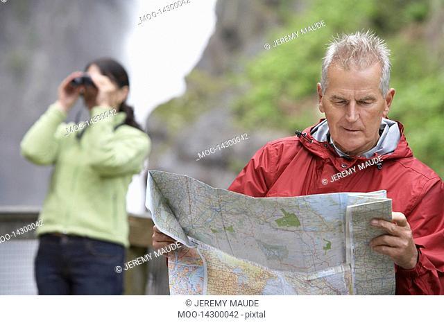 Man and woman in mountains man reading map woman looking through binoculars