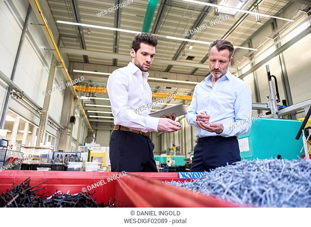 Two businessmen with tablet in factory standing at containers with shred
