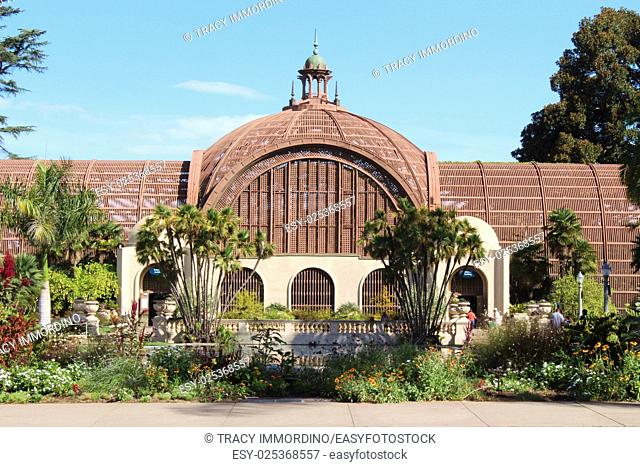Front view of the Botanical Building with pond, flowers, shrubs and trees framing the building in Balboa Park, San Diego, California, USA