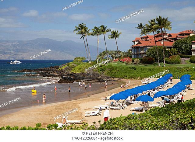 Beach umbrellas on Polo Beach and a snorkel boat off the shore; Wailea, Maui, Hawaii, United States of America