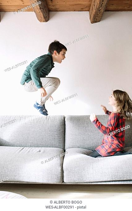 Boy jumping in the air on the couch while his sister watching him
