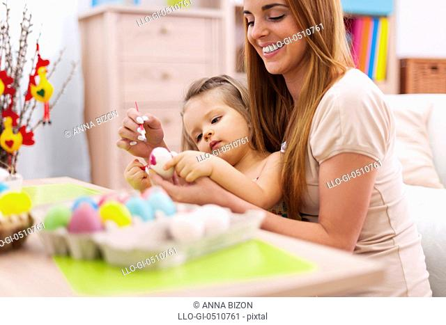 Mother and baby painting easter eggs. Debica, Poland