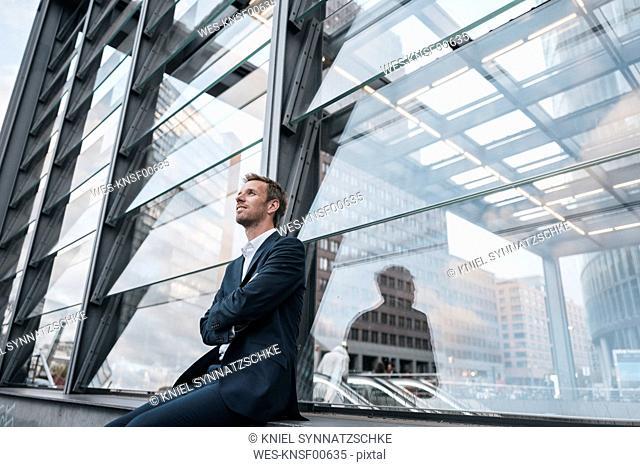 Germany, Berlin, businessman sitting at Potzdamer Platz watching something