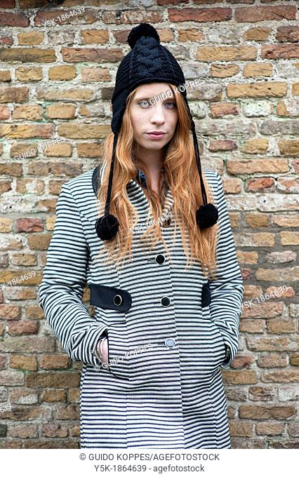 Breda, Netherlands. Young, fashionable and redheaded woman in a city-park, leaning against a wall
