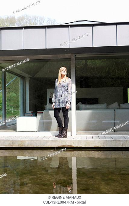 teenager in front of modern house