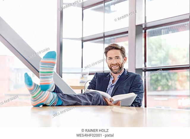 Portrait of smiling businessman putting his feet on the table reading book