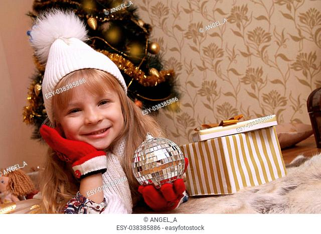 Cute girl in knitted hat and gloves holding Christmas ball