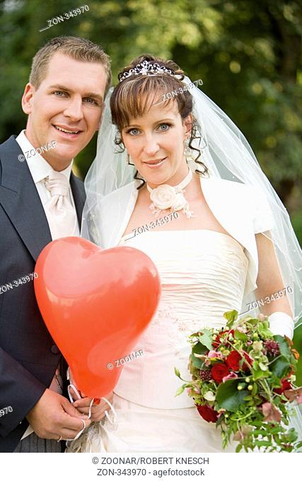 Portrait eines jungen Brautpaars mit einem Luftballon in Herzform