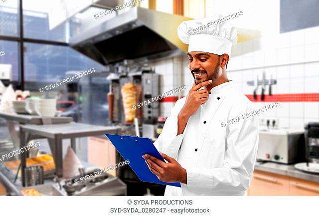 indian chef with menu on clipboard at kebab shop