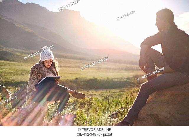 Young couple hiking, resting and writing in sunny remote field