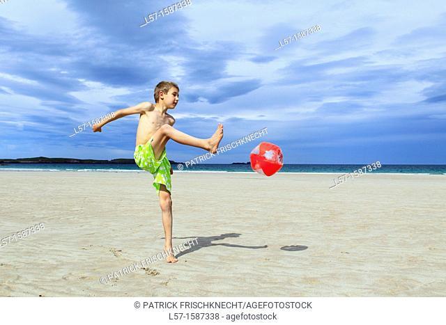 boy playing on sandy beach, Sutherland, Scotland