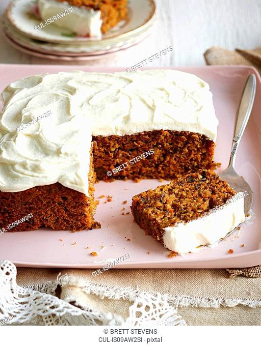 Carrot cake with frosted icing on pink dish