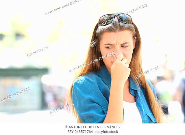 Girl covering nose in the middle of a contaminated city street