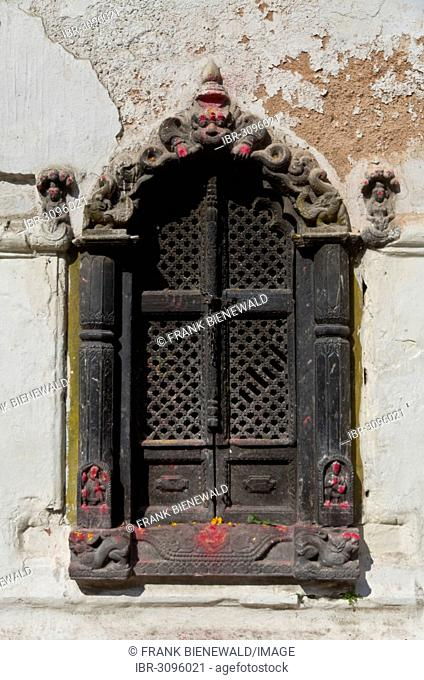 Ornate carved wooden window of a small shrine in the hills above Pashupatinath Temple