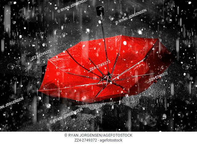 Upside down umbrella left staind to the falling rain