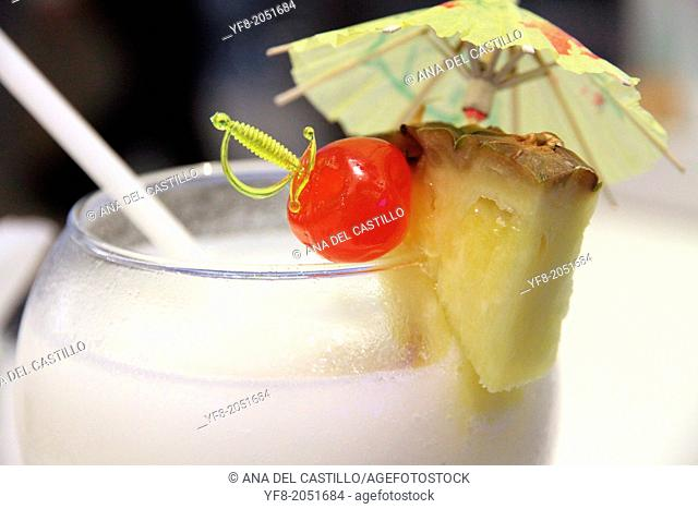 Cocktail with paper umbrella and fruit