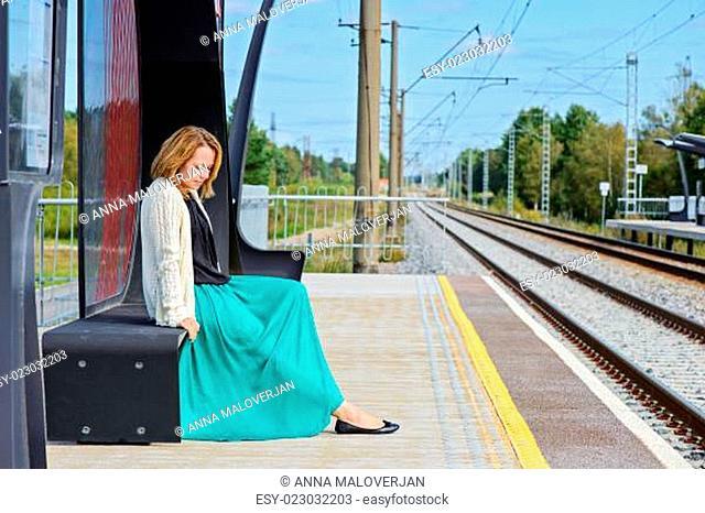 Female sitting and waiting train on the platform