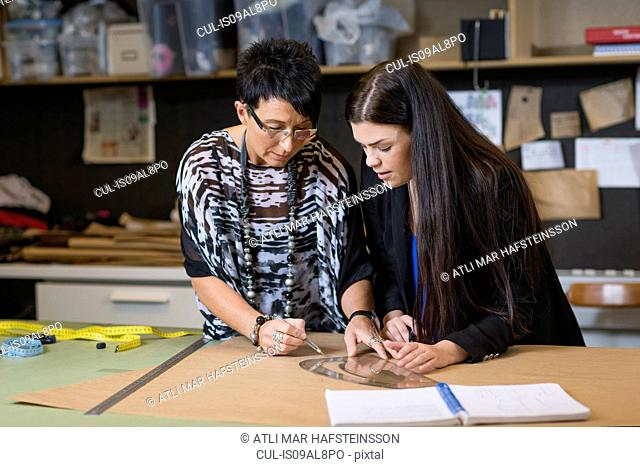 Two seamstresses using curved ruler on dressmakers pattern in workshop