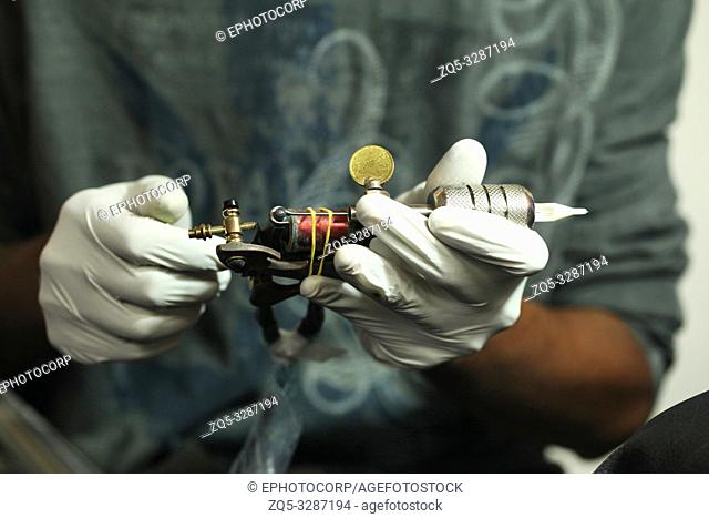 Man in white gloves holding instrument to tattoo, Maharashtra, India