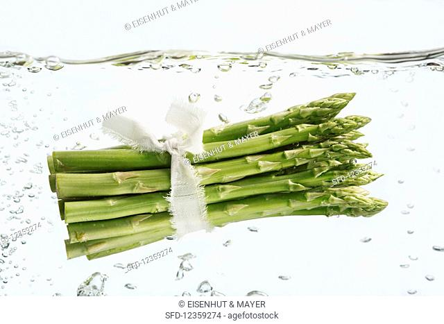 A bundle of asparagus in bubbly water