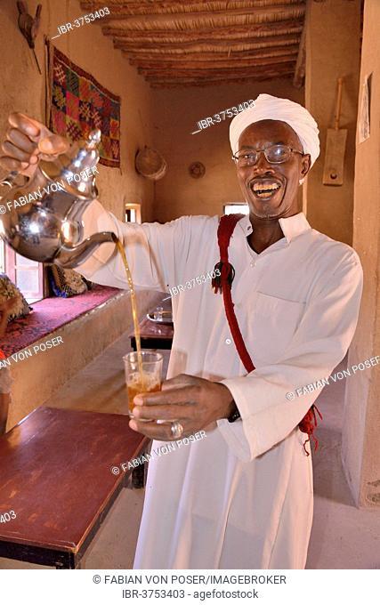 Man pouring tea into a glass, Merzouga, Meknès-Tafilalet region, Morocco