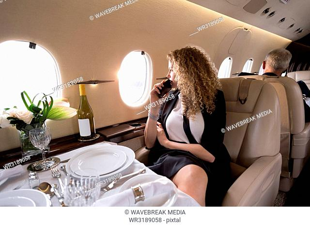 Businesswoman looking through window while travelling in private jet