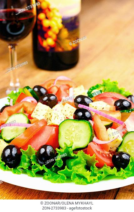 Greek salad and glass of red wine on the kitchen table