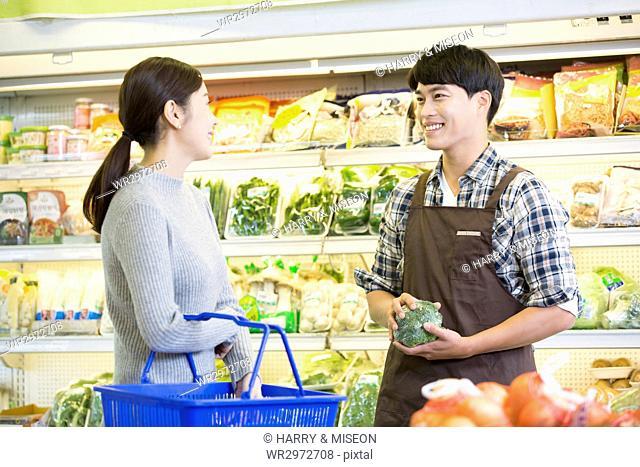 Smiling customer and salesman at supermarket