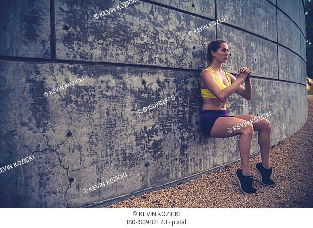Young woman leaning against wall outdoors, doing squats
