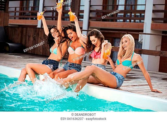 Joyful women drinking cocktails and having fun near swimming pool