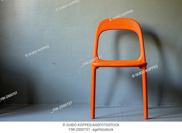 Tilburg, Netherlands. Single orange chair against a grey studio wall. The chair is an vintage Ikea chair Urban