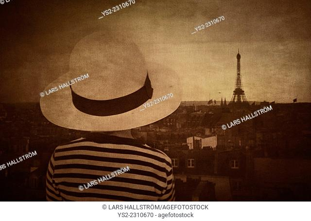 Back view of little girl with hat watching Paris skyline. Dark and moody setting