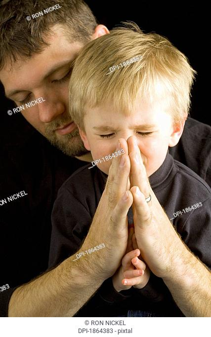 Father praying with son