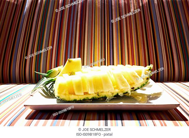 Plate of sliced pineapple on striped sofa