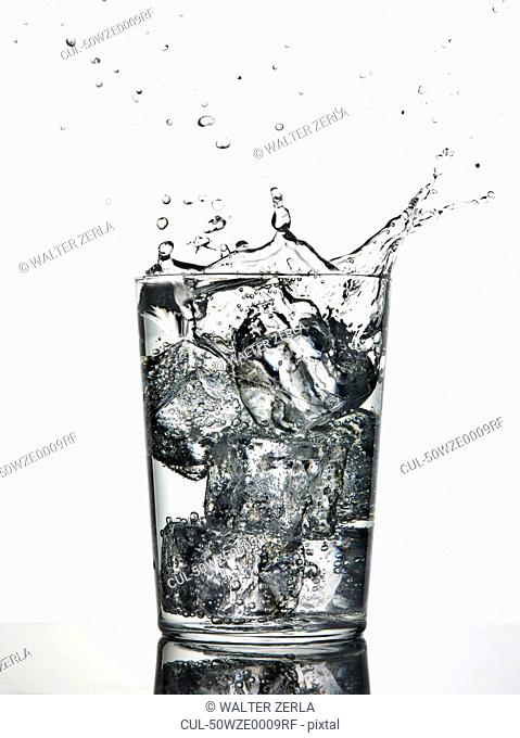 Ice cubes splashing into fizzy drink