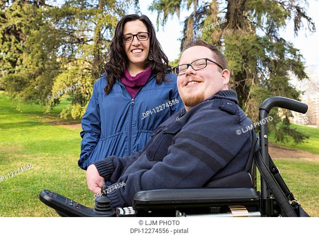 Disabled husband with his wife posing for a picture in a park in autumn; Edmonton, Alberta, Canada