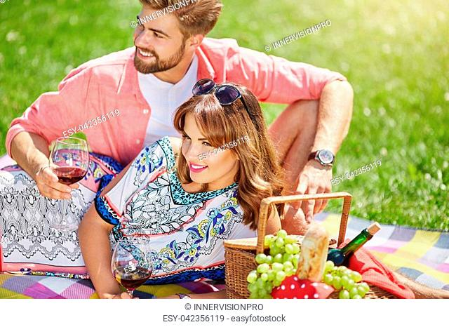 A photo of young, happy couple relaxing on the picnic at the park with grapes and a bottle of wine