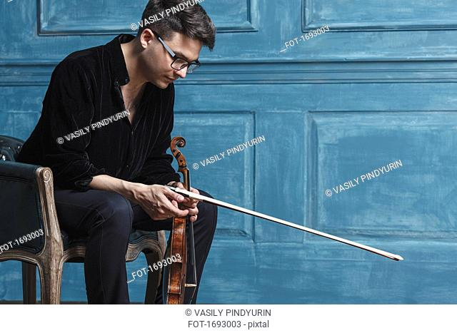 Young man holding violin while sitting on chair by blue wall