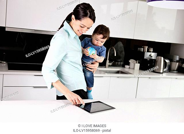 A mother and her baby son looking at a digital tablet, baby holding a globe ball