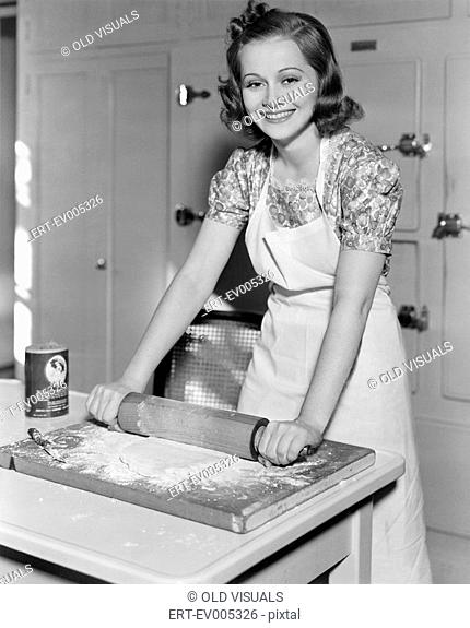 Young woman rolling out dough in the kitchen All persons depicted are not longer living and no estate exists Supplier warranties that there will be no model...